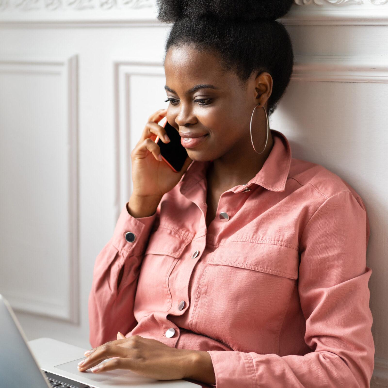 Focused African American millennial woman talking on phone, work